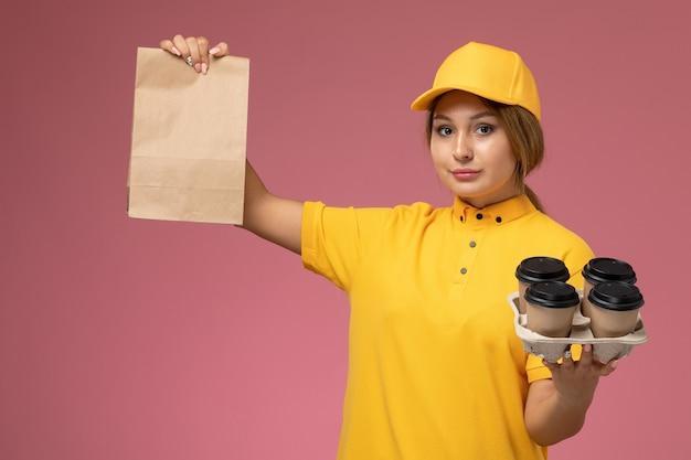 Vorderer blick weiblicher kurier in gelbem einheitlichem gelbem umhang, der lebensmittelverpackung mit plastikkaffeetassen auf rosa hintergrunduniformlieferarbeitsfarbauftrag hält