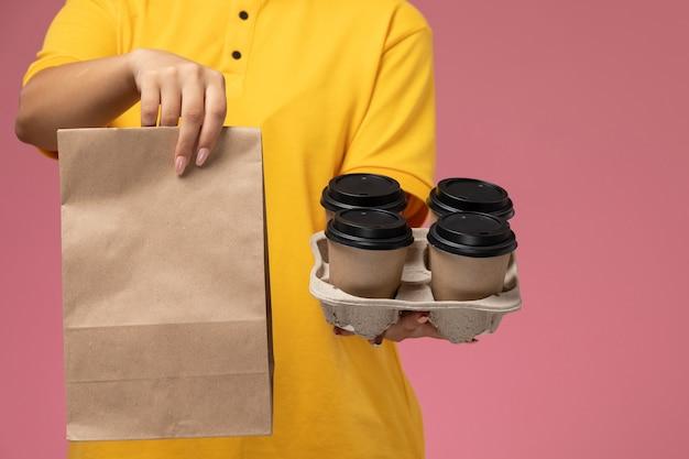 Vorderer blick weiblicher kurier in gelbem einheitlichem gelbem umhang, der lebensmittelverpackung und kaffee auf der rosa hintergrunduniformlieferarbeitsjobfarbe hält