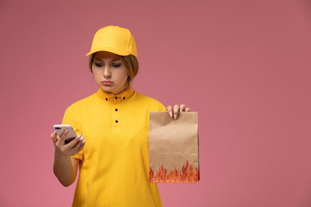 Vorderer blick weiblicher kurier in gelbem einheitlichem gelbem umhang, der lebensmittelverpackung unter verwendung eines telefons auf rosa hintergrunduniformlieferarbeitsfarbauftrag hält