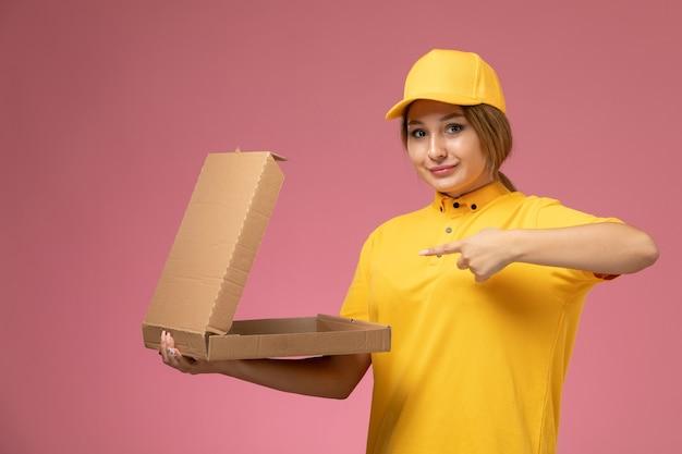 Vorderer blick weiblicher kurier in gelbem einheitlichem gelbem umhang, der leere lebensmittelverpackung auf dem rosa hintergrunduniformlieferungsarbeitsjob hält