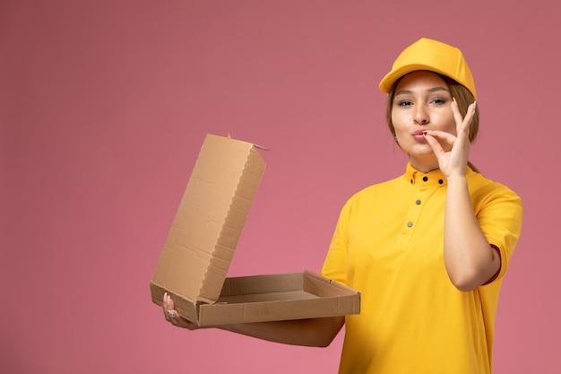 Vorderer blick weiblicher kurier in gelbem einheitlichem gelbem umhang, der lieferpaket auf dem rosa hintergrunduniformlieferungsarbeitsauftrag öffnet