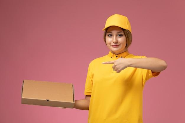 Vorderer blick weiblicher kurier in gelbem einheitlichem gelbem umhang, der nahrungsmittelbox auf rosa hintergrunduniformlieferarbeitsfarbe hält