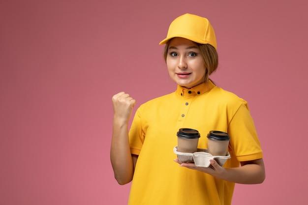 Vorderer blick weiblicher kurier in gelbem einheitlichem gelbem umhang, der plastikkaffeetassen auf dem hellen hintergrund einheitliche lieferarbeitsjobfarbe hält
