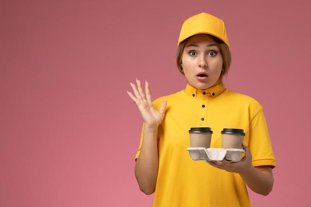 Vorderer blick weiblicher kurier in gelbem einheitlichem gelbem umhang, der plastikkaffeetassen auf dem rosa hintergrunduniformlieferungsarbeitsjob hält