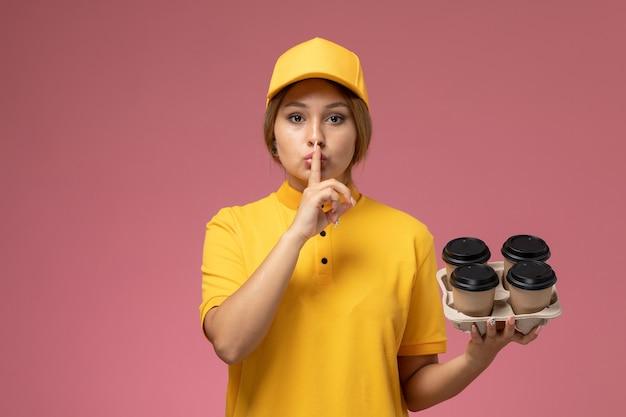 Vorderer blick weiblicher kurier in gelbem einheitlichem gelbem umhang, der plastikkaffeetassen hält und schweigenzeichen auf rosa hintergrunduniformlieferarbeitsfarbauftrag zeigt