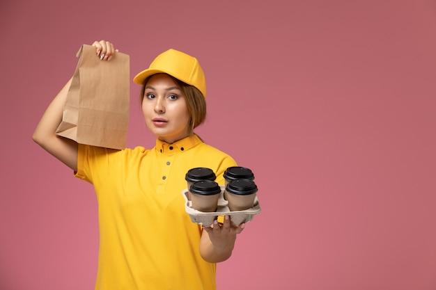 Vorderer blick weiblicher kurier in gelbem einheitlichem gelbem umhang, der plastikkaffeetassen und lebensmittelverpackung auf dem rosa bodenuniformlieferarbeitsfarbauftrag hält