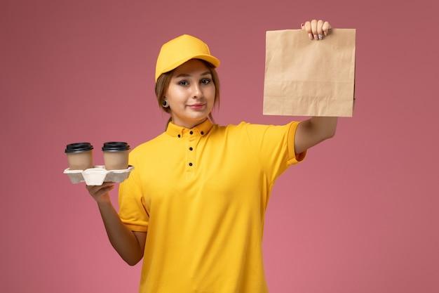 Vorderer blick weiblicher kurier in gelbem einheitlichem gelbem umhang, der plastikkaffeetassen und lebensmittelverpackung auf rosa schreibtischuniformlieferungsfarbfoto weiblich hält