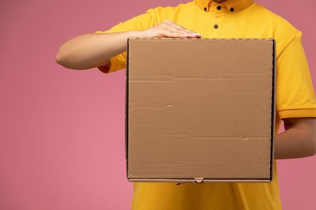 Vorderer blick weiblicher kurier in gelbem einheitlichem gelbem umhang, der plastiknahrungsmittelbox auf rosa hintergrunduniformlieferarbeitsjobfarbe hält