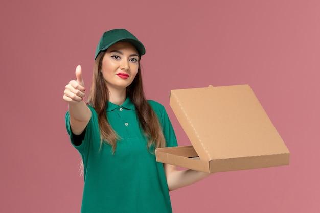 Vorderer blick weiblicher kurier in grüner uniform, die nahrungsmittellieferbox auf rosa wandfirmenserviceuniformlieferungsarbeitsarbeit hält