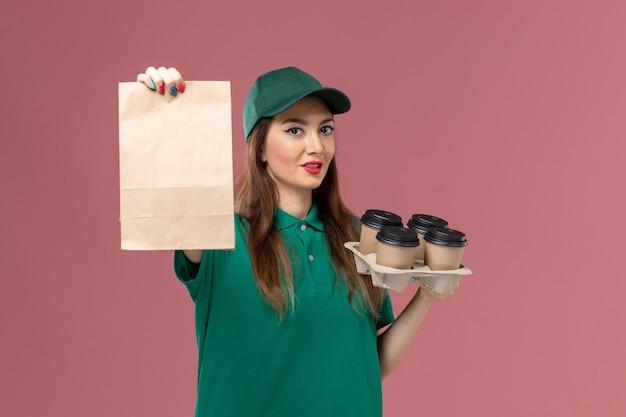 Vorderer blick weiblicher kurier in grüner uniform und umhang, der lebensmittelpaket und lieferkaffeetassen auf rosa schreibtischserviceuniformlieferarbeiter hält