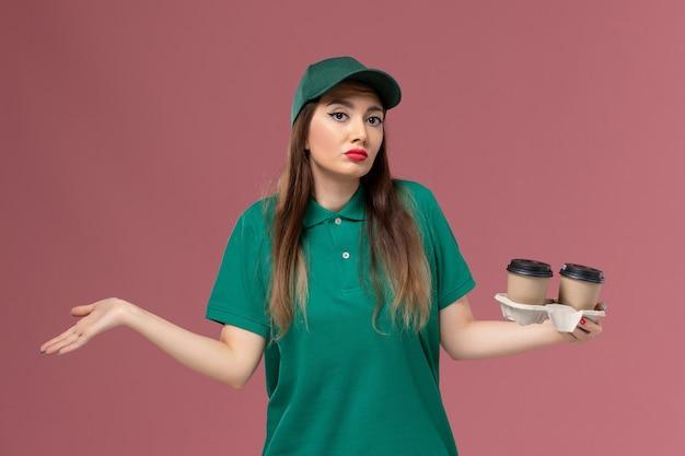 Vorderer blick weiblicher kurier in grüner uniform und umhang, der lieferkaffeetassen auf der rosa wandfirmenservicejobuniformlieferungsarbeitsmädchen hält