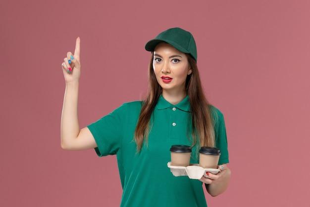 Vorderer blick weiblicher kurier in grüner uniform und umhang, der lieferung kaffeetassen auf rosa wand firmenservice jobuniform lieferarbeiter weibliches arbeitsmädchen hält
