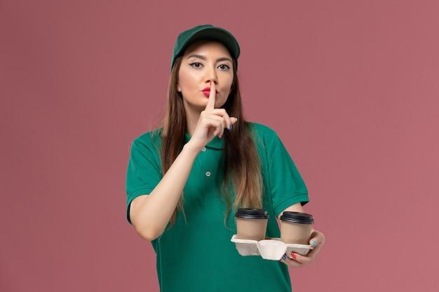 Vorderer blick weiblicher kurier in grüner uniform und umhang, der lieferung kaffeetassen auf rosa wand firmenservice uniform lieferung weibliches arbeitsmädchen hält