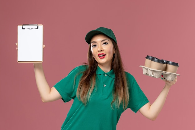 Vorderer blick weiblicher kurier in grüner uniform und umhang, der notizblock und lieferkaffeetassen auf rosa wanddienstuniformlieferungsjobmädchen hält