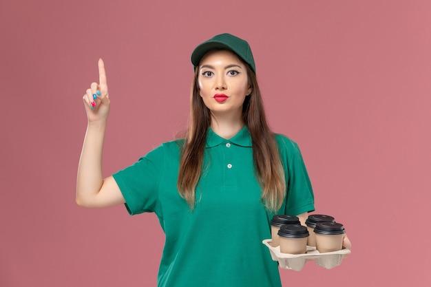 Vorderer blick weiblicher kurier in grüner uniform und umhang, die braune lieferkaffeetassen auf dem rosa wanddienstuniformlieferauftrag halten