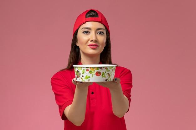 Vorderer blick weiblicher kurier in rotem uniformumhang mit lieferschüssel auf ihren händen auf hellrosa schreibtischservice-liefermitarbeiter