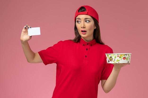 Vorderer blick weiblicher kurier in rotem uniformumhang mit lieferschüssel und weißer karte auf ihren händen auf hellrosa wand, arbeitsuniform-liefermitarbeiter