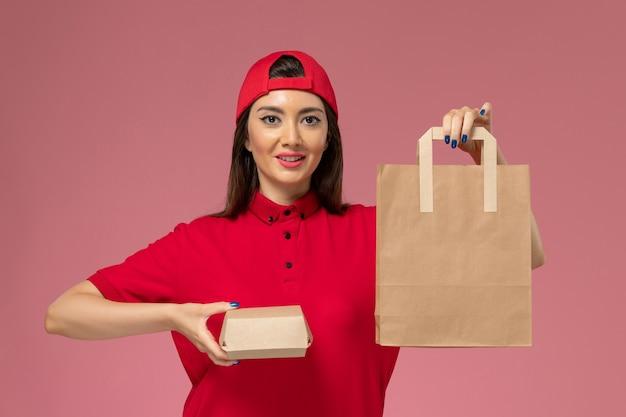Vorderer blick weiblicher kurier in rotem uniformumhang mit verschiedenen lieferpaketen auf ihren händen auf rosa wand, uniformjoblieferungsangestellter