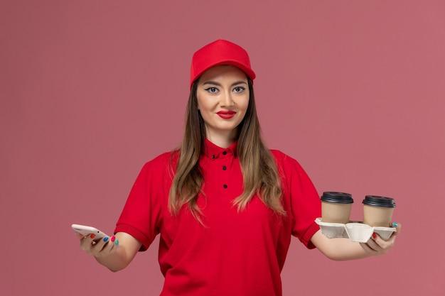 Vorderer blick weiblicher kurier in roter uniform, die lieferkaffeetassen hält und telefonlächeln auf rosa hintergrundarbeiterjobdienstlieferuniform verwendet