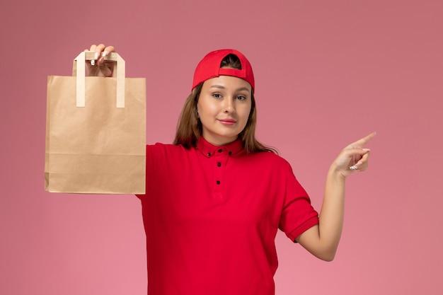 Vorderer blick weiblicher kurier in roter uniform und umhang, der lieferpapierpaket auf rosa wand hält, einheitlicher zustellungsjobdienst
