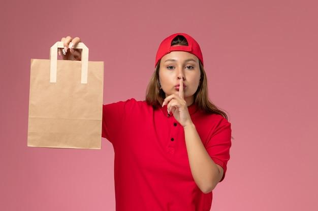 Vorderer blick weiblicher kurier in roter uniform und umhang, der lieferpapierpaket auf rosa wand hält, jobuniform-lieferservice