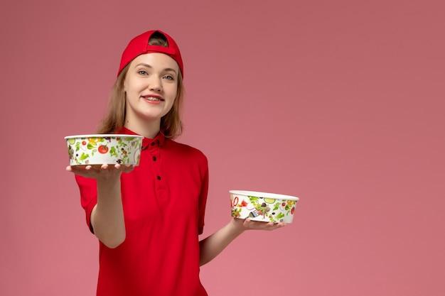 Vorderer blick weiblicher kurier in roter uniform und umhang, der lieferschalen mit lächeln auf hellrosa schreibtischdienstuniformlieferung hält