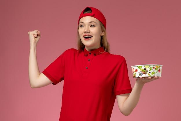 Vorderer blick weiblicher kurier in roter uniform und umhang, der lieferschüssel hält und auf rosa wand, dienstuniformlieferung jubelt