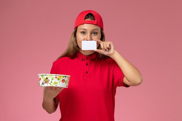 Vorderer blick weiblicher kurier in roter uniform und umhang, der lieferschüssel und karte auf rosa wand hält, einheitliche lieferservicearbeit