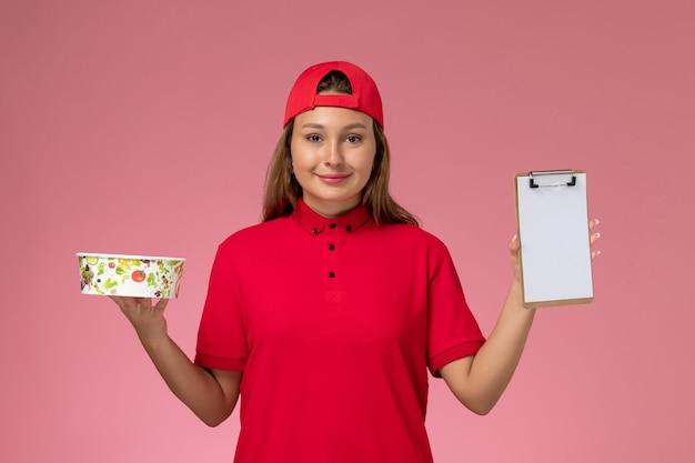 Vorderer blick weiblicher kurier in roter uniform und umhang, der notizblock und lieferschüssel auf rosa hintergrunduniformjob-lieferservice hält