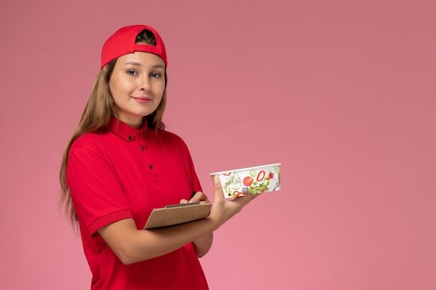 Vorderer blick weiblicher kurier in roter uniform und umhang, der notizblock und lieferschüssel auf rosa hintergrunduniformlieferdienstjobarbeiter hält