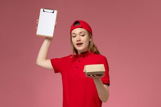 Vorderer blick weiblicher kurier in roter uniform und umhang, die kleines liefernahrungsmittelpaket mit notizblock auf rosa schreibtischlieferdienstfirma-jobuniform halten