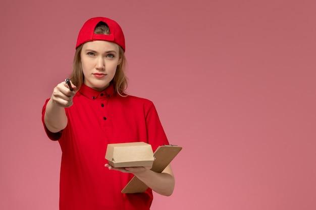 Vorderer blick weiblicher kurier in roter uniform und umhang, die kleines liefernahrungsmittelpaket mit notizblock und stift auf rosa wand halten, serviceuniform-lieferauftrag