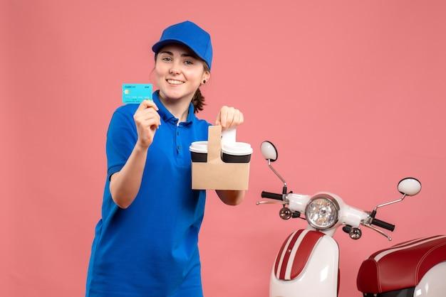 Vorderer blick weiblicher kurier mit kaffee und bankkarte auf rosa arbeit lieferung uniform service arbeiter pizza frau fahrrad