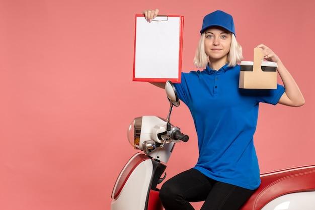 Vorderer blick weiblicher kurier mit kaffeetassen auf dem rosa lieferservice arbeiten farbarbeiteruniformjob