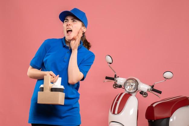 Vorderer blick weiblicher kurier mit lieferkaffee auf dem rosa arbeitslieferdienstarbeiterfrauenfahrraduniformjob
