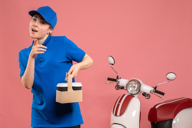 Vorderer blick weiblicher kurier mit lieferkaffee auf rosa arbeit lieferservice arbeiter fahrrad uniform job