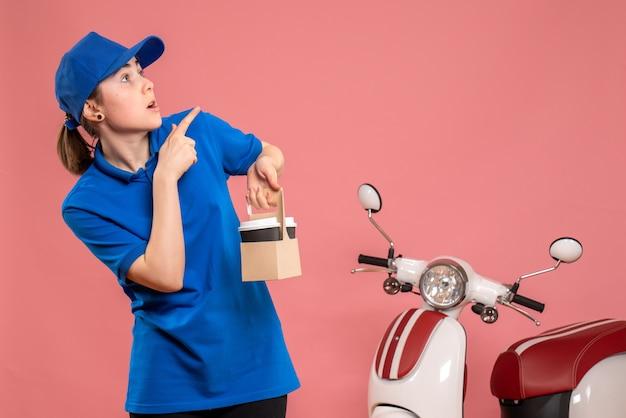 Vorderer blick weiblicher kurier mit lieferkaffee auf rosa arbeit lieferung arbeiter frau fahrrad uniform job