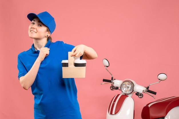 Vorderer blick weiblicher kurier mit lieferkaffee auf rosa arbeitsservicearbeiterfrau fahrraduniformjob