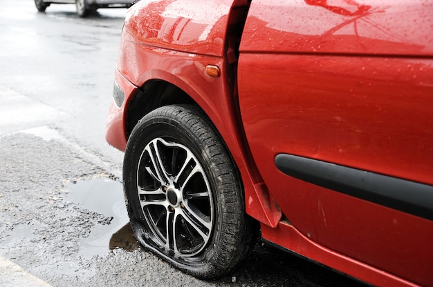 Vorderer linker flügel und rad des roten autounfalls