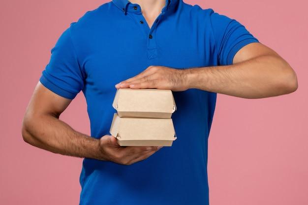 Vorderer nahansicht junger männlicher kurier im blauen uniformumhang, der kleine liefernahrungsmittelpakete an der rosa wand hält, servicemitarbeiter liefert