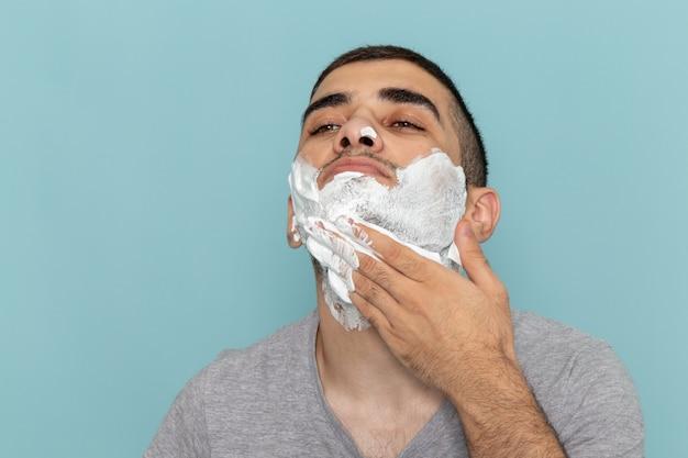 Vorderer nahansicht junger mann im grauen t-shirt, das sein gesicht mit weißem schaum zum rasieren auf der eisblauen wand bartschaum-rasiermesser rasiert