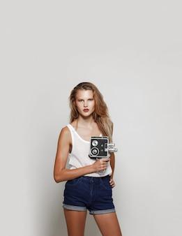 Vorderes bild einer blonden jungen frau, die in weißer modekleidung posiert, in die kamera schaut und eine retro-kamera in der hand hält.