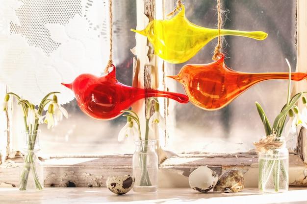 Vorderes fenster mit glasvögeln und schneeglöckchen