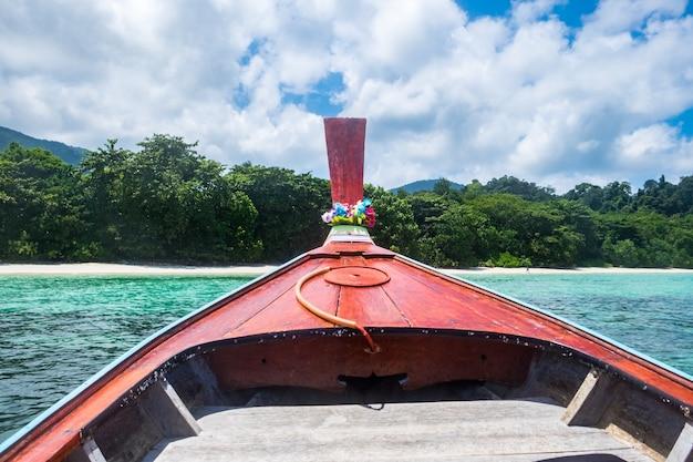 Vorderes hölzernes longtail-boot und kristallklares meer mit blauem himmel