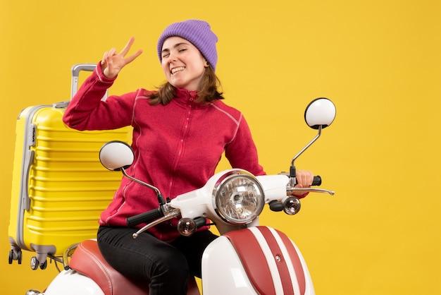 Vorderes junges mädchen der ansicht mit dem blinzelnden auge auf moped gestikulierendes siegeszeichen