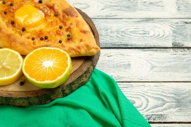 Vorderes nahes ansicht köstliches eierbrot, das mit käse auf einem rustikalen grauen schreibtisch gebacken wird