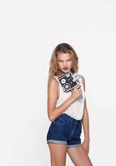 Vorderes porträt der blonden jungen frau, die in weißer modekleidung posiert, wegschaut und eine retro-kamera in der hand hält. platz kopieren.
