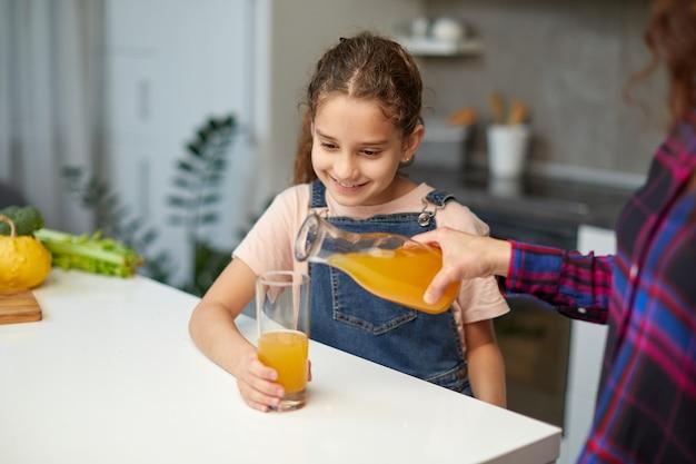 Vorderes porträt der nahaufnahme einer hand gießt süßen orangensaft des kleinen mädchens.