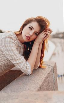 Vorderes porträt einer nachdenklichen eleganten jungen frau mit rotem haar tragen e im stylingbeigekleid, das auf balkon, hellem hintergrund steht.