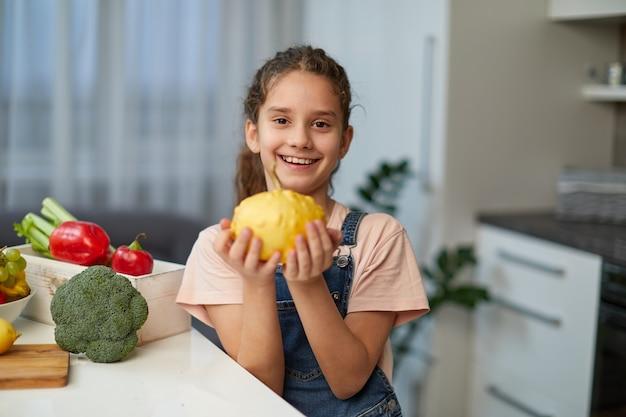 Vorderes porträt eines hübschen kleinen mädchens mit lockigem haar, das eine jeans und ein t-shirt trägt, einen gelben kürbis hält und am tisch in der küche sitzt.
